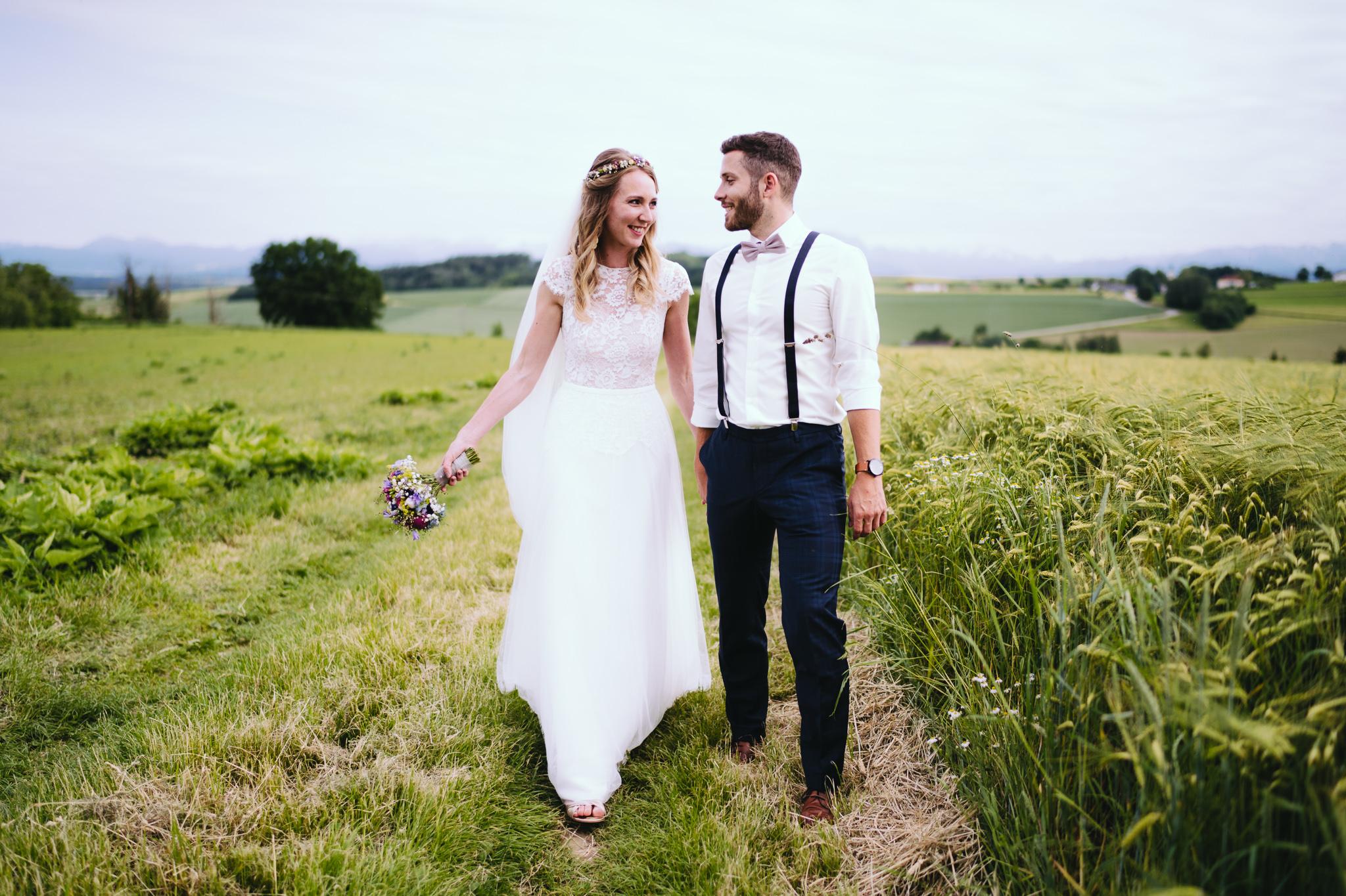 Hochzeitspaar schlendert über Feldweg