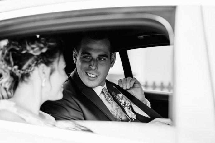 Bräutigam sitzt im Auto und sieht die Braut an