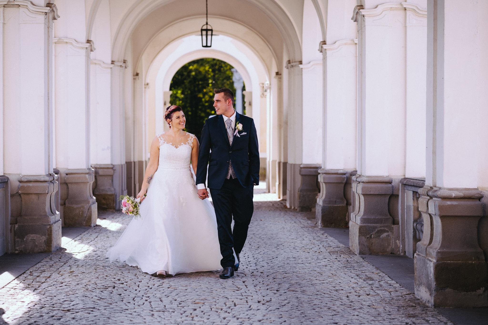 Brautpaar schlendert über Brücke im Schloss Lamberg